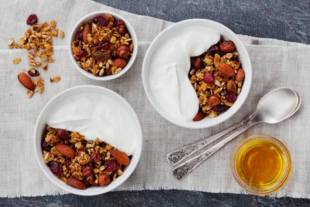 Selbst gemachte Jogurtschüssel mit Granola auf schwarzer Tabelle, gesundes und Diätfrühstück, Draufsicht