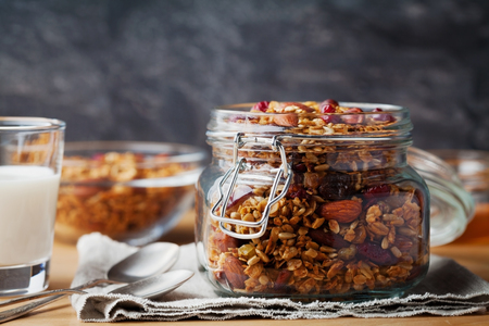 arandanos rojos: granola casera en un frasco en la mesa rústica, desayuno saludable de muesli harina de avena, nueces, semillas y frutos secos
