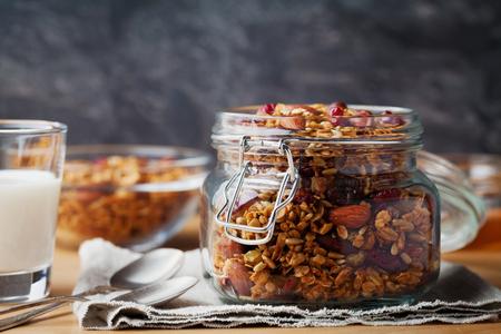 Hausgemachtem Müsli im Glas auf rustikalen Tisch, gesundes Frühstück Haferflocken Müsli, Nüsse, Samen und getrockneten Früchten