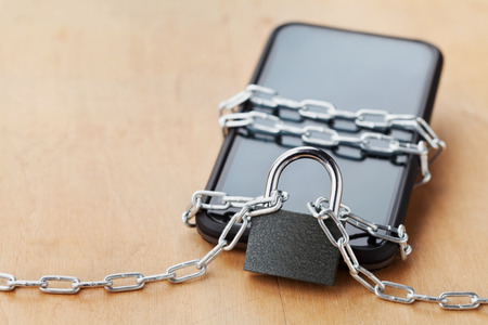 lock and chain: Smartphone tied chain with lock on wooden table, gadget and digital devices detox concept Stock Photo