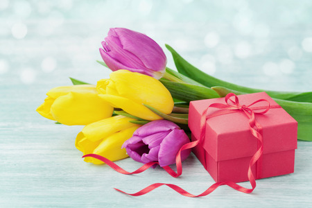 flowers bokeh: Gift box and tulip flowers on rustic table for March 8, International Womens day, Birthday or Mothers day, beautiful spring card