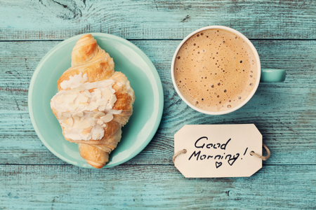morning: Coffee mug with croissant and notes good morning on turquoise rustic table from above, cozy and tasty breakfast, vintage toned