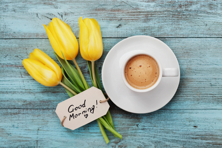 Coffee mug with yellow tulip flowers and notes good morning on blue rustic table from above, breakfast on Mothers day or Womens day Stockfoto