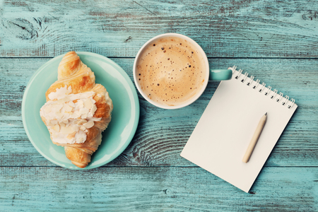 Coffee mug with croissant and empty notebook and pencil for business plan and design ideas on turquoise rustic table from above, cozy and tasty breakfast, vintage toned
