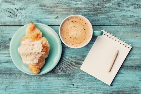 breakfast: Taza de café con croissant y cuaderno vacío y el lápiz de diseño del plan y las ideas de negocio en la mesa rústica de color turquesa desde arriba, el desayuno agradable y sabroso, vintage tonificado