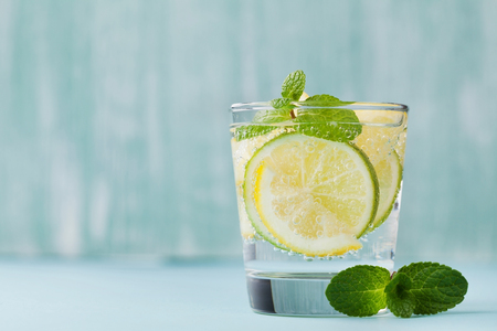 Mineral infused water with limes, lemons, ice and mint leaves on blue background, homemade detox soda water recipe