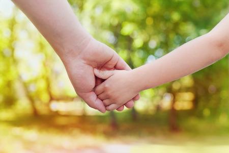 niños felices: Padres mano que sostiene a su pequeño niño en un día soleado al aire libre, familia unida y el concepto de infancia feliz, hermoso fondo bokeh