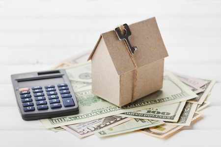 building loan: Model of cardboard house with key, calculator and cash dollars. House building, loan, real estate. Cost of public utilities, insurance, rent or buying a new home concept Stock Photo