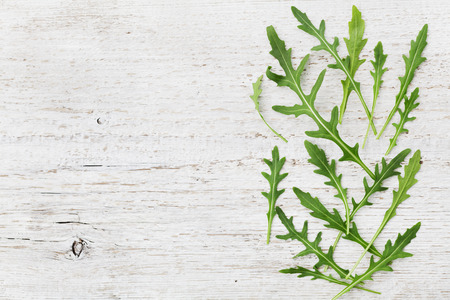 roquette: Rucola, salad rocket, rucoli, rugula, colewort, roquette or arugula on wooden rustic table, top view