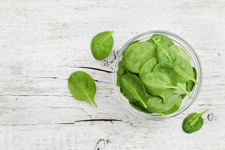 De spinaziebladeren van de baby in kom op witte rustieke lijst, organisch en gezond voedsel, hoogste mening Stockfoto