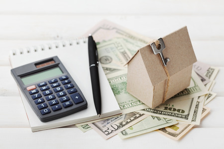 Model of cardboard house with key, calculator, notebook, pen and cash dollars.
