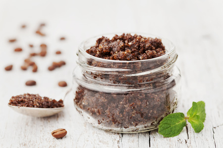 Body scrub of ground coffee, sugar and coconut oil in glass jar on white rustic table, homemade cosmetic for peeling and spa care Standard-Bild