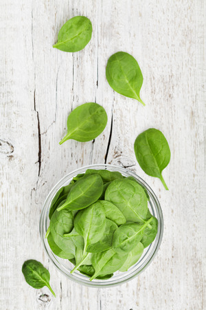 Baby spinach leaves in bowl on white rustic table, organic and healthy food, top view