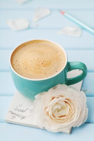capuchino: Taza de café con la flor de la primavera y notas de buena mañana en el fondo rústico azul, desayuno el día de la madre o el día de las mujeres