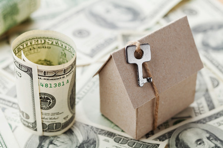 housewarming: Model of cardboard home with key and dollar money. House building, insurance, housewarming, loan, real estate, cost of housing or buying a new home concept. Stock Photo