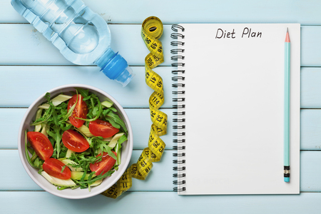 Diet plan, menu or program, tape measure, water and diet food of fresh salad on blue background, weight loss and detox concept, top view Banco de Imagens