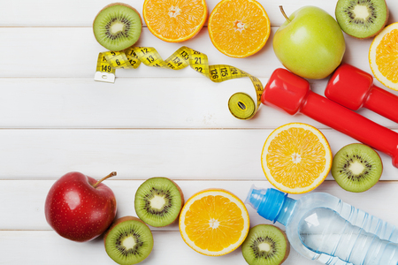 weight loss plan: Diet plan, menu or program, tape measure, water, dumbbells and diet food of fresh fruits on white background, weight loss and detox concept, top view Stock Photo