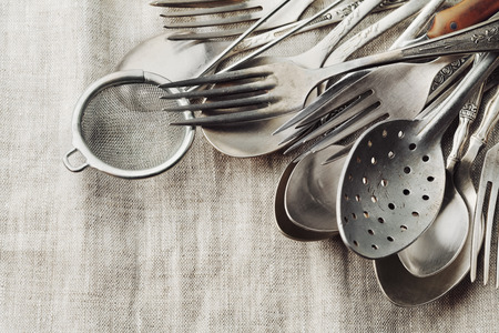menu tool: Vintage cutlery on rustic background, old kitchen tools, retro colors