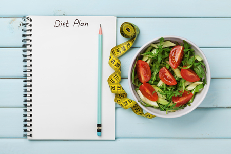 Dieet plan, menu of programma, meetlint en dieet van verse salade op een blauwe achtergrond, gewichtsverlies en detox concept, bovenaanzicht