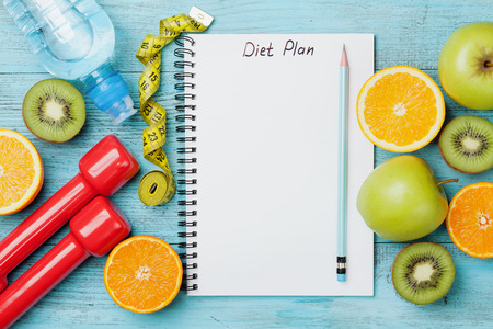 weight loss plan: Diet plan, menu or program, tape measure, water, dumbbells and diet food of fresh fruits on blue background, weight loss and detox concept, top view Stock Photo