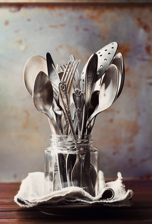 cutleries: Vintage cutlery in jar on rustic background, old kitchen tools, retro colors
