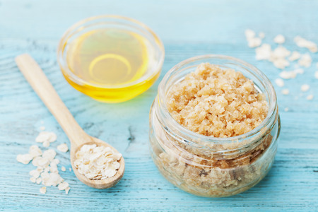 exfoliate: Body scrub of oatmeal, sugar, honey and oil in glass jar on blue rustic table, homemade cosmetic for peeling and spa care