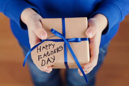 Childrens hands holding a gift or present box with kraft paper and tied blue ribbon tag on Happy fathers day, holiday concept
