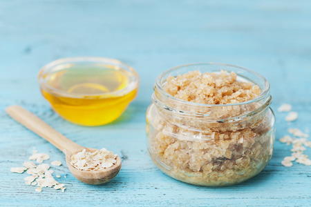 Body scrub of oatmeal, sugar, honey and oil in glass jar on blue rustic table, homemade cosmetic for peeling and spa care