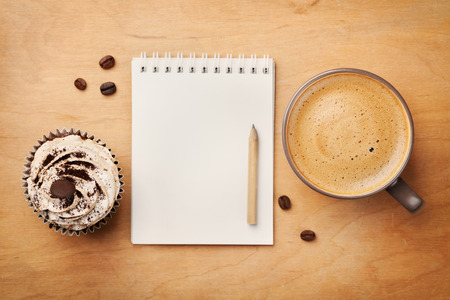 Coffee mug with cupcake, notebook and pencil on rustic table from above, cozy and sweet breakfast, good morning or have a nice day concept 写真素材