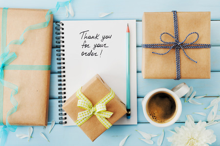 orders: Notebook with the words Thank you for your order, pencil and gift or present box packed in kraft paper on blue wooden table, top view Stock Photo