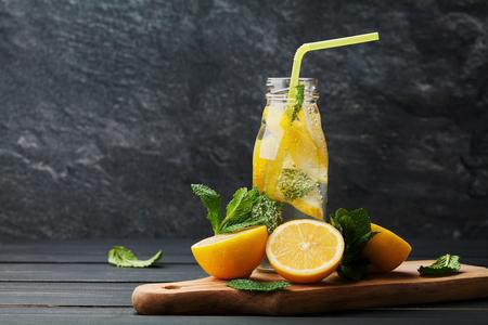 Lemonade drink of soda water, lemon and mint leaves in jar on black background