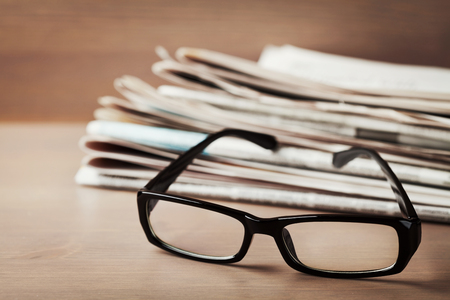 poor eyesight: Eyeglasses and stack of newspapers on wooden desk for themes of ophthalmology, poor vision and reading Stock Photo