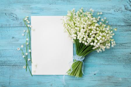 azul turqueza: Ramo de flores de lirio de los valles y la hoja de papel vacía en la mesa rústica de color turquesa desde arriba, hermosa tarjeta de cosecha, vista desde arriba, copia espacio para el texto, para establecer planos