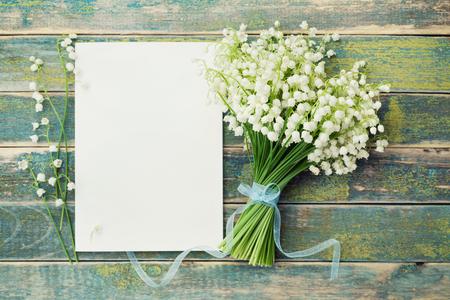 Boeket bloemen lelie van de vallei en leeg vel papier op rustieke tafel van hierboven, mooie vintage kaart, bovenaanzicht, kopieer ruimte voor tekst, plat