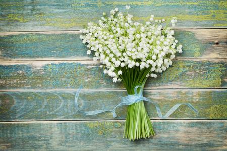 flor de lis: Hermoso ramo de flores lirio de los valles en la mesa de madera de época desde arriba, fondo rústico Foto de archivo