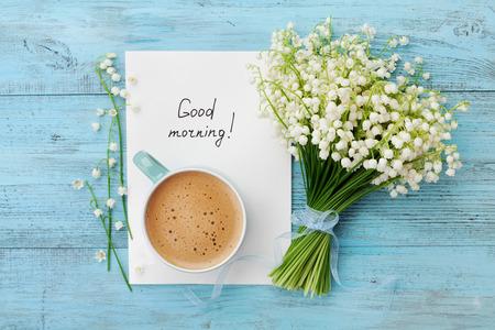 La taza de café con el ramo de flores de lirio de los valles y toma nota de los buenos días en la mesa rústica de color turquesa desde arriba, hermoso desayuno, tarjeta de cosecha, vista desde arriba, en posición plana