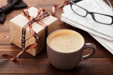 Ochtend kopje koffie, cadeau, krant, bril en bowtie op houten bureau voor ontbijt op Happy Fathers Day