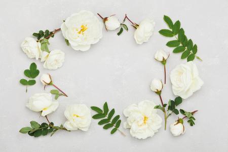 Frame van witte roos bloemen en groene bladeren op lichtgrijze achtergrond van bovenaf, mooi bloemenpatroon, vintage kleur, vlakke lay-styling