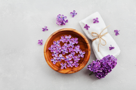 composition: Spa and  wellness composition with perfumed lilac flowers water in wooden bowl and terry towel on gray stone background, aromatherapy, top view, flat lay