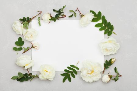 Il bianco è aumentato fiori, foglie verdi e foglio di carta pulita su sfondo grigio chiaro dall'alto, bellissimo disegno floreale, colore d'epoca, stile distesi
