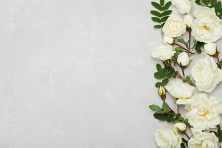 De grens van witte roze bloemen en groene bladeren op lichtgrijze achtergrond van hierboven, mooi bloemenpatroon, uitstekende vlakke kleur, legt