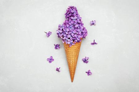 Eis der lila Blüten in der Waffel auf hellgrauem Hintergrund von oben, schöne Blumenarrangement, Oldtime, flach lag Styling Standard-Bild - 59628020