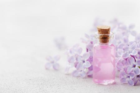 Frasco de vidrio con agua de rosas y flores de color lila para spa y aromaterapia, copia espacio para el texto