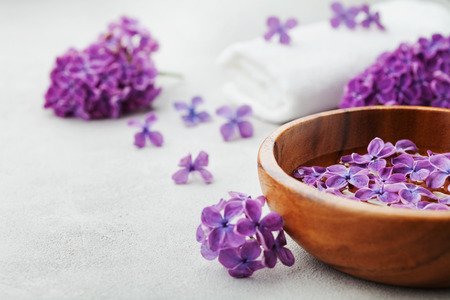 perfumed: Spa and  wellness composition with perfumed lilac flowers water in wooden bowl and terry towel on gray stone background, aromatherapy