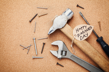 note board: Working tools and note for Happy Fathers Day, cork board background, top view, flat lay