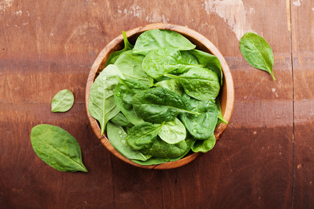 baby spinach: Baby spinach leaves in wooden bowl on old rustic table, organic food, top view Stock Photo