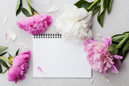 Mooie roze en witte pioenbloemen met lege notitieblok op grijze stenen achtergrond, kopieer ruimte voor uw tekst of ontwerp, bovenaanzicht, vlakke lay