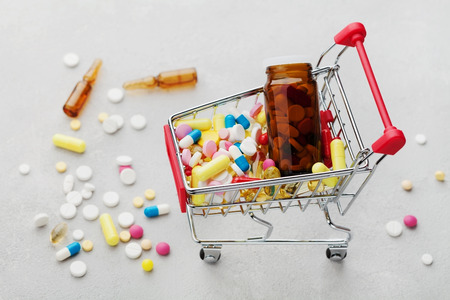 narcotism: Shopping cart full of pharmaceutical drug and medicine pills on light background