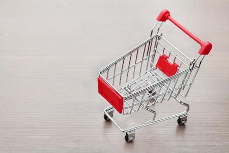 carretilla de mano: Carro de compras vacío en el fondo de madera Foto de archivo