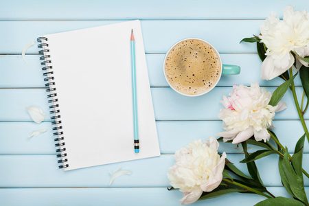 Morning coffee mug, empty notebook, pencil and white peony flowers on blue wooden table, cozy summer breakfast, top view, flat lay